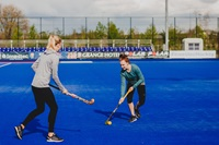 Two women playing hockey and the Lea Valley Tennis and Hockey Centre