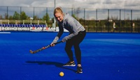 A woman playing hockey at Lee Valley Hockey and Tennis Centre